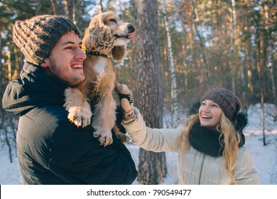 Carefree happy young couple with their dog having fun together in snow in winter woodland throwing snowballs at each other during a mock fight