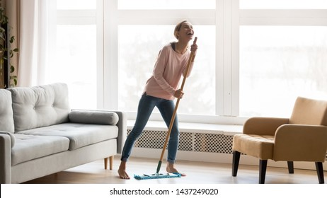 Carefree happy young woman cleaning house living room have fun dancing with mop, smiling overjoyed millennial girl feel excited enjoy making home chores sing entertain using floor broom or Swiffer