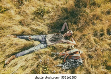 Carefree happy young woman wearing sunglasses lying on green grass meadow enjoying sun on her face. Enjoying nature sunset. Freedom traveling. Enjoyment. Relaxing on meadow at sunrise. Daydreaming