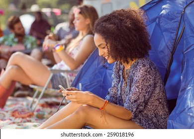 Carefree hipster sending text message at a music festival