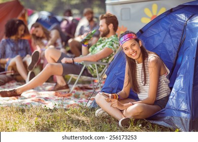 Carefree hipster smiling on campsite at a music festival