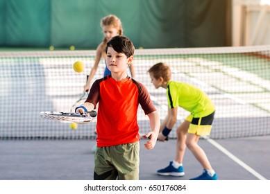 Carefree kids enjoying playtime on tennis court