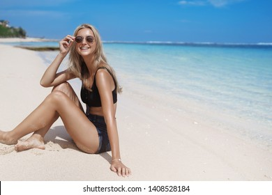 Carefree laughing joyful blond tanned girl sit sandy beach look camera touch sunglasses enjoy holiday summer vacation tourist tour, stay hotel resort near ocean, delighted great holidays