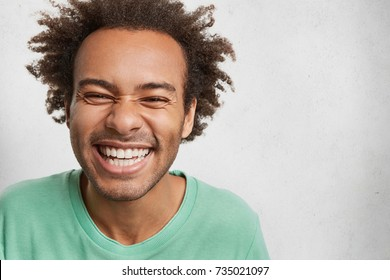 Carefree life, youth and happiness concept. Glad positive male with bushy hair, dark skin and perfect teeth, loughs out loudly at good joke or funny strory, grins in camera, isolated on white wall