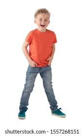 CAREFREE LITTLE BOY IN ORANGE T SHIRT SMILING HAPPY WITH HANDS IN POCEKTS OF BLUE JEANS STANDING ISOLATED ON WHITE BACKGROUND