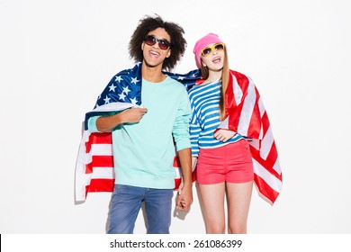 Carefree and in love. Funky young couple covering with American flag and smiling while standing against white background