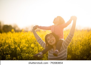 Carefree mother carrying baby girl on her shoulders in the rapeseed field