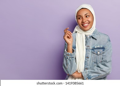 Carefree optimistic female with toothy smile, being in high spirit, wrapped in white scarf, wears fashionable denim jacket, looks away, poses over purple background, blank space area for information