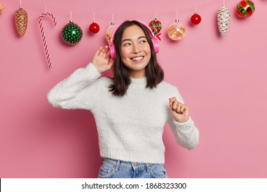 Carefree positive Asian girl wears stereo headphones and enjoys listening favorite music on New Years Eve dressed in casual white jumper poses against pink background with hanging christmas toys - Shutterstock ID 1868323300