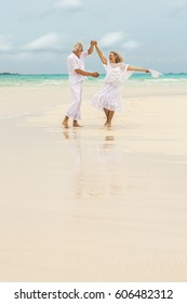 Carefree retired senior Caucasian couple wearing white clothes dancing barefoot on summer travel resort beach
