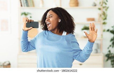 Carefree Singer. Portrait of african lady singing and using cell phone as mic, dancing and wearing earbuds