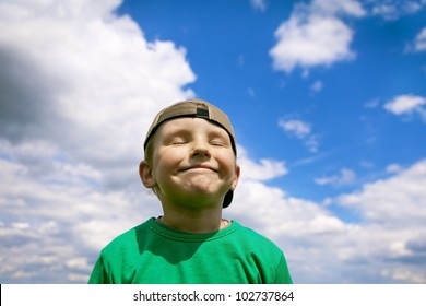 Carefree, smiling boy in the blue sky and white clouds. Proud and pleased with himself, a charming little urchin. Portrait