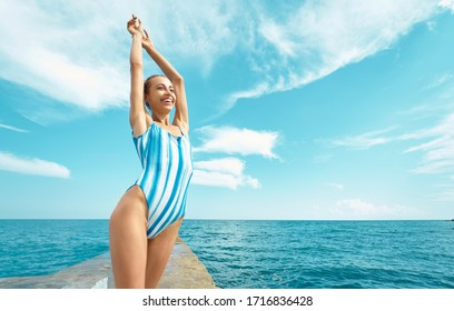 carefree smiling woman in swimsuit standing with raised hands and sunbathing against sea ocean view and blue sky. concept summer sea vacation, travel and freedom