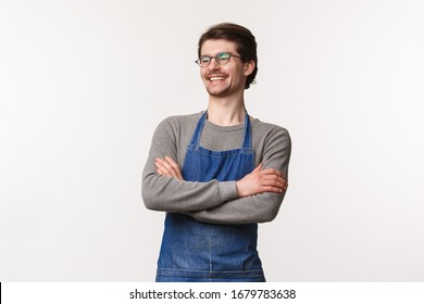 Carefree smiling young outgoing male bartender laughing with coworker standing in apron with hands crossed chest, look away delighted, manage own small business cafe, stand white background