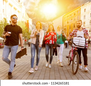 carefree students walking down the street in summer city centre enjoy coffee to go hanging out. they have skateboard and bike. the sunshine is bright. passetsby walk in the background.