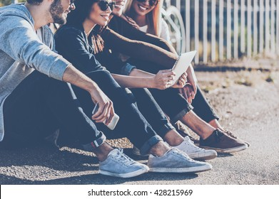 Carefree time with best friends. Close-up of group of young smiling people bonding to each other and looking at digital tablet while sitting outdoors together