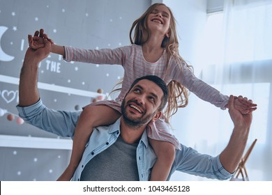 Carefree time with dad. Cheerful father carrying his daughter on shoulders and smiling while spending free time at home