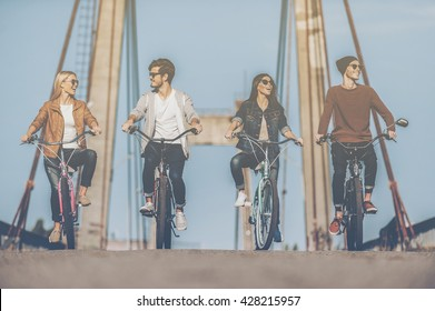 Carefree time with friends. Four young people riding bicycles along the bridge and smiling