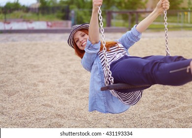 Carefree trendy young woman on a swing leaning back and grinning at the camera with a vivacious smile