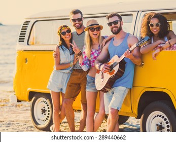 Carefree weekend with friends. Group of young cheerful people bonding to each other and smiling while leaning at their retro styled minivan with sea in the background