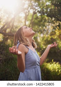 Carefree woman with arms out enjoying sunlight in forest