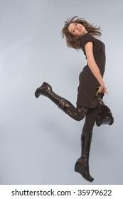 Carefree woman in black kicking leg up behind her.