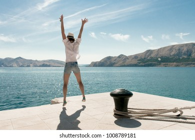 Carefree woman jumping at beach. Beautiful travel destination. Baska harbour, Krk island, Croatia.