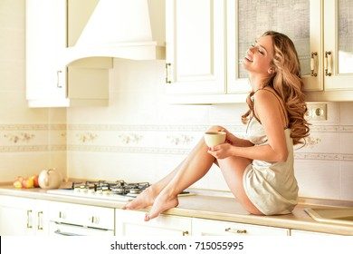 Carefree  woman in the kitchen interior in the morning. Breakfast.