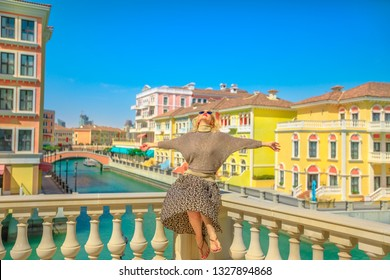 Carefree woman on balcony overlooking canals of Venice, a Venetian style waterfront village. Caucasian happy tourist enjoys Qanat Quartier in The Pearl-Qatar, icon of Doha, Persian Gulf, Middle East.