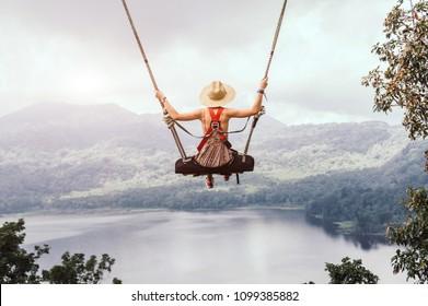 Donna spensierata sull'altalena in un paesaggio stimolante. Concetto da sogno
