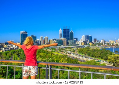 Carefree woman overlooking Perth Water, a section of Swan River, and central business district of Perth from Kings Park, the most popular visitor destination in Western Australia. Blue sky, copy space