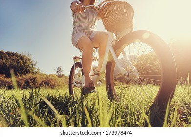 Carefree woman riding bicycle in park having fun on summer afternoon