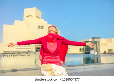 Carefree woman sitting in front of fountain of famous museum along the Corniche near Dhow Harbor in Qatari capital. Caucasian tourist enjoying in Doha, Middle East, Arabian Peninsula in Arabian Gulf.