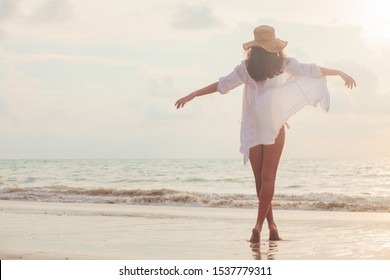 carefree woman in straw hat walking in the sunset on the beach. vacation vitality healthy living concept