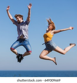 Carefree young couple friends jumping by sea ocean water. Happy woman and man having fun. Summer happiness and freedom.