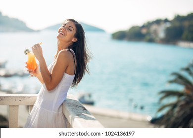 Carefree young female on holiday summer vacation having fun on a sunny day,relaxing with ocean view,listening waves,enjoying summer with refreshing drink.Love summer.Deserved vacation
