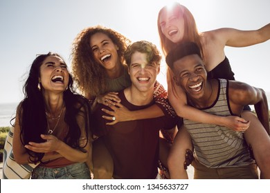 Carefree young friends enjoying weekend together outdoors. Men carrying women in their back and laughing.