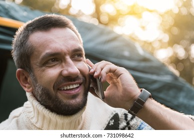 Carefree young man talking on mobile phone in forest