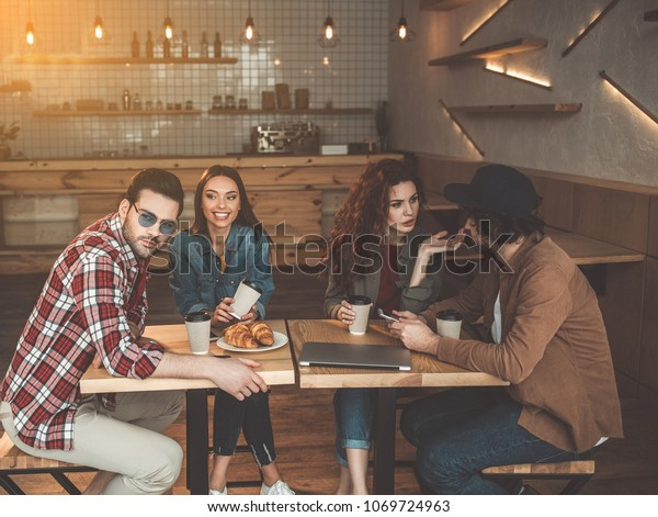 Carefree young men and women are having double date. They are sitting at desk in cafe and drinking coffee. Guy and girl are talking while other couple is smiling