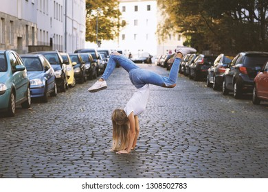 carefree young woman doing spontaneous handstand in the middle of city street