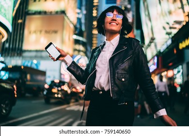 Carefree young woman in eyewear with night city light reflection dancing on crowded street listening music via smartphone and earphones, cheerful hipster girl enjoying favorite song feeling excited