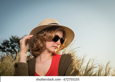 Carefree young woman in a hat with evening sun