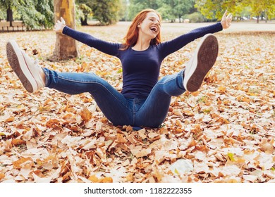 Carefree young woman having fun in an autumn park flinging her legs and arms in the air while sitting on the ground amongst the fallen leaves