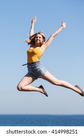 Carefree young woman jumping by sea ocean water. Happy girl having fun. Summer happiness and freedom.