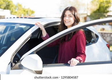 Carefree young woman smiling while getting in her new car