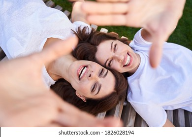 Carefree young womans enjoyinghappy time together. Girls laying on the bench and laughing out loud