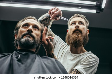 Careful bearded barber standing near his client and putting hands up while combing his hair