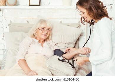 Careful caregiver measuring patients blood pressure at home