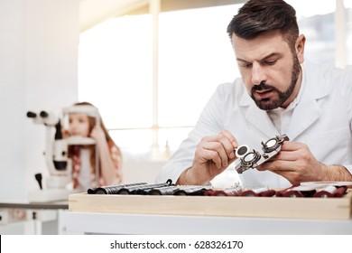 Careful dedicated optician repairing the lenses