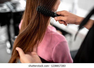 Careful hairdresser touching long hair of the female client while brushing it in beauty salon